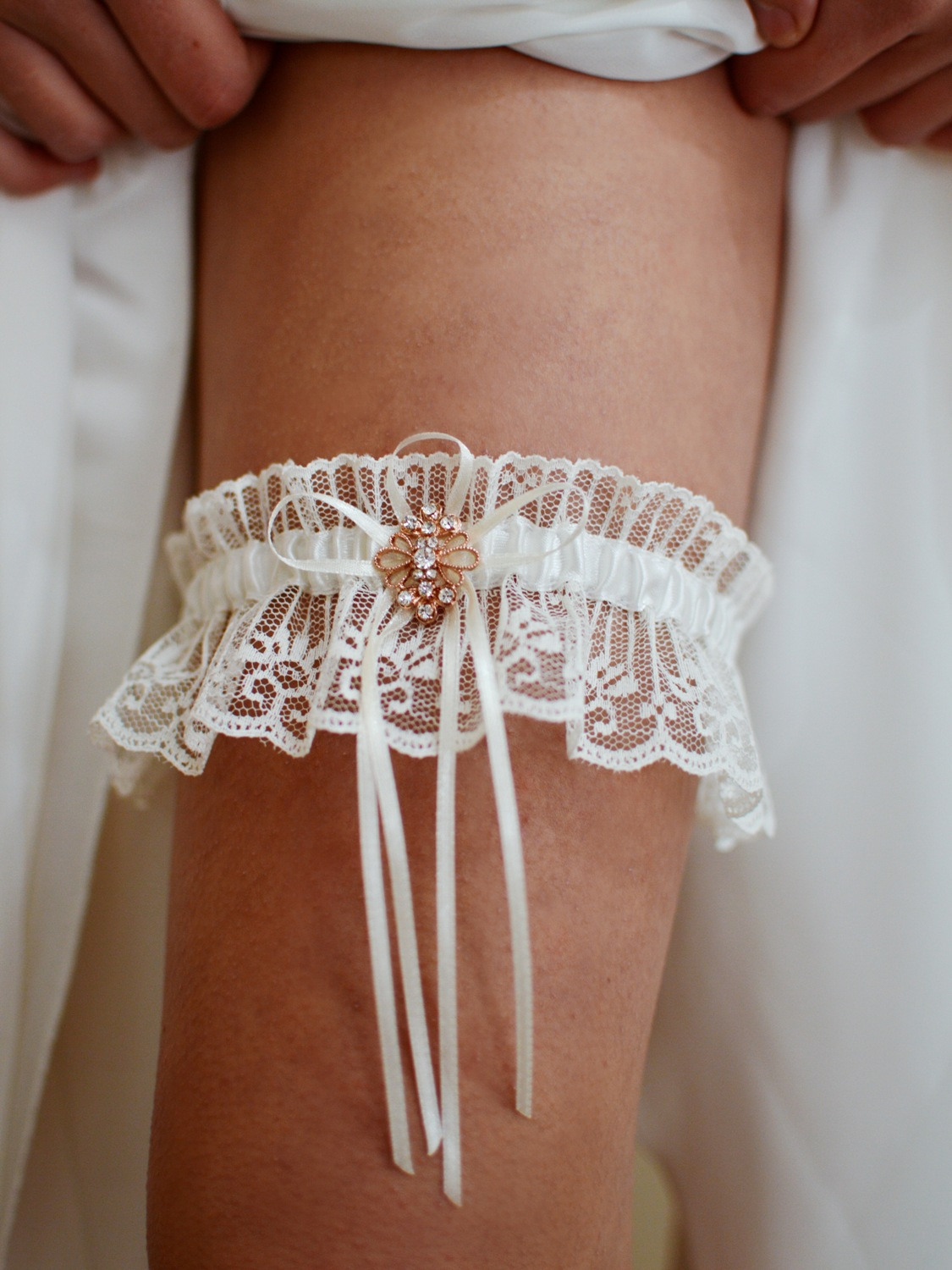 Gorgeous ivory lace bridal garter with rose gold brooch on leg TLG516