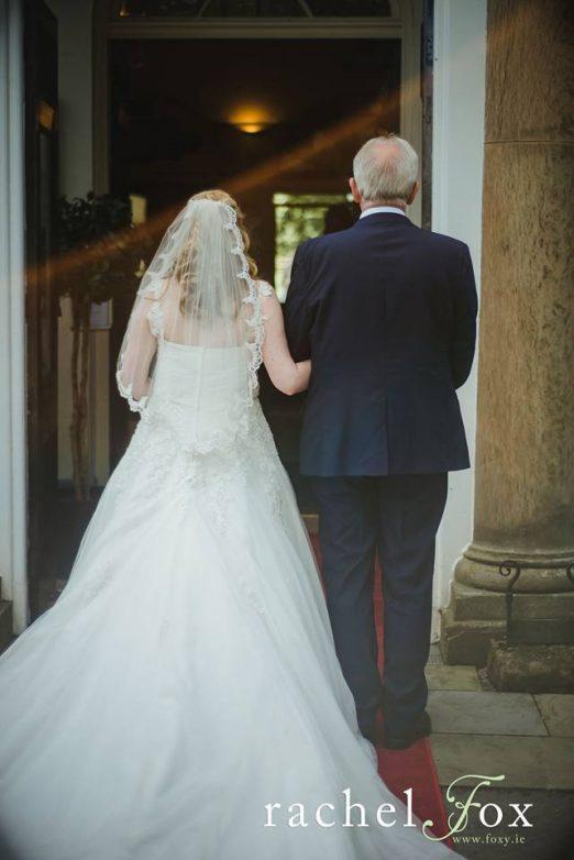Emma wears a bespoke waist length veil with a scalloped lace edge